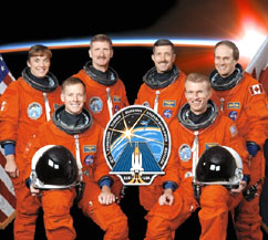 The STS-115 space shuttle crew of six pose in orange shuttle launch and entry suits