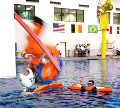 Astronaut Joe Tanner, wearing an orange shuttle launch and entry suit, flips backwards into a large pool of water