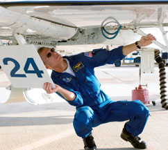 Brent Jett kneels under a plane as he checks to make sure it is ready to fly