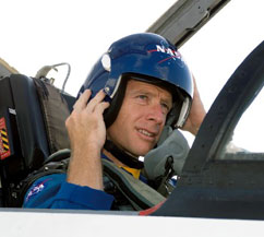 Astronaut Christopher Ferguson wears a blue helmet as he sits in the cockpit of a jet