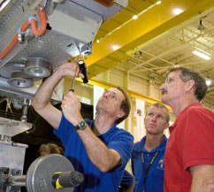 Three astronauts look carefully at a piece of shuttle training equipment