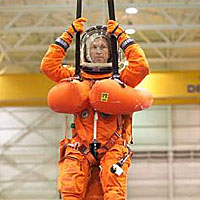 Astronaut Brent Jett in orange launch and entry suit suspended in a parachute harness