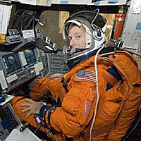 Astronaut Chris Ferguson sitting in a simulation of a pilot's station in one of the full-scale space shuttle trainers
