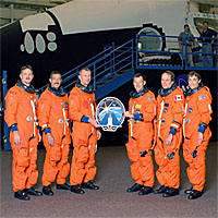 The STS-115 crew poses next to the Crew Compartment Trainer with a large version of their mission patch