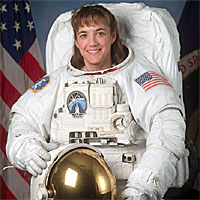 Astronaut Heidemarie Stefanyshyn-Piper poses in a bulky white spacesuit
