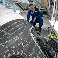 Astronaut Joseph Tanner crouching on a platform looks at the front of the space shuttle
