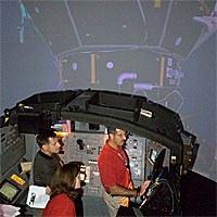 Three astronauts stand observing a computer monitor during a simulation in the systems engineering simulator