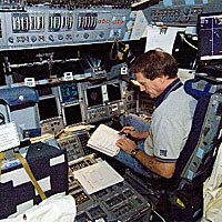 Astronaut Steven MacLean studies crew notes while sitting in a shuttle trainer