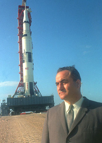 Dr. Rocco A. Petrone stands in front of a Saturn V rocket.