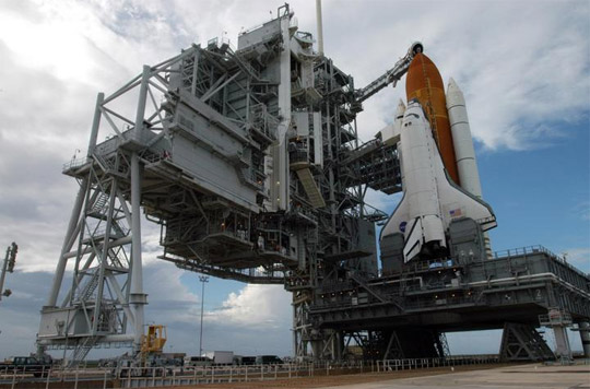 The rotating service structure is rolled away from Space Shuttle Atlantis.