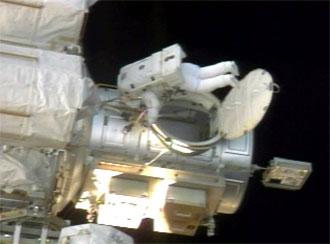 La especialista Heide Stefanyshyn-Piper sale de la esclusa de aire de la EEI al comienzo de la tercera salida al espacio de la misión STS-115. NASA TV.
