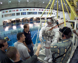 A group of NASA workers help astronaut Joseph Tanner as he stands in a bulky white space suit next to a large pool of water