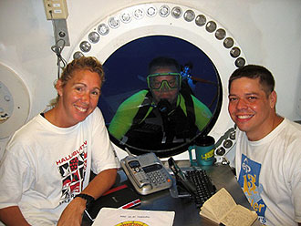JSC2006-E-40695 -- NEEMO 11 astronaut/aquanauts Sandra Magnus (left) and Robert Behnken (right) with astronaut/aquanaut Timothy Kopra outside the habitat