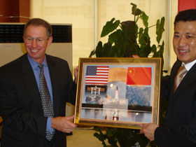 Administrator Griffin presents a picture montage with a flown American and Chinese flags to President and CEO, China Academy of Space Technology, Dr. Yuan Jiajun.