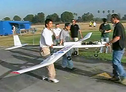 Fuel cell-powered, remotely piloted airplane is carried by students.