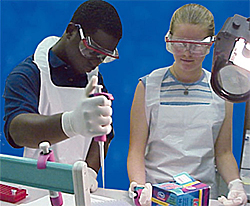 Two students wear safety glasses, gloves and aprons as one works with a pipette