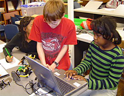 Two students work with a laptop and a small robotic vehicle