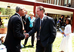 Lou Mayo and President Bush shake hands outside a school