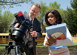 Lou Mayo and a student use a telescope to study the sun