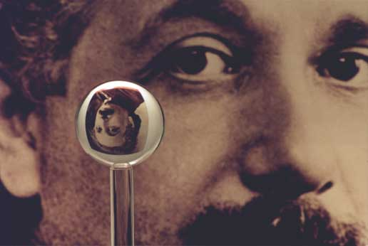 Close up of a clear, uncoated quartz rotor reflecting a poster of Albert Einstein.