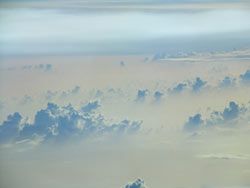 Cumulus clouds can be seen poking through the tops of the dust layer, which is seen as a milky white haze.