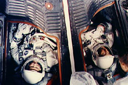 Astronauts L. Gordon Cooper Jr. (left) and Charles Conrad Jr. are seen in the Gemini 5 spacecraft in white room at Pad 19 just after insertion.