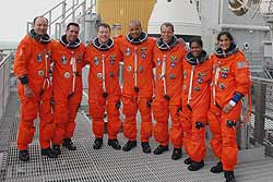 The Discovery astronauts pose in front of the white solid rocket boosters and external tank.