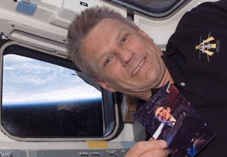 Piers Sellers with photo of Stephen Hawking on board the space shuttle during mission STS