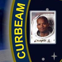 A close-up view of the name Curbeam on the STS-116 mission patch and a photo of Robert Curbeam