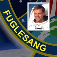 A close-up view of the name Fuglesang on the STS-116 mission patch and a photo of Christer Fuglesang