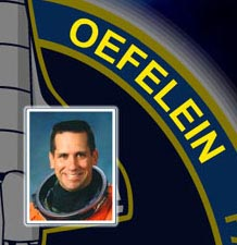 A close-up view of the name Oefelein on the STS-116 mission patch and a photo of William Oefelein