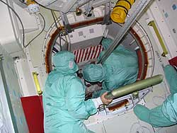 Stowage crew lowers spacewalking suit box into orbiter.