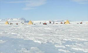 Tents can be seen on the snow plain