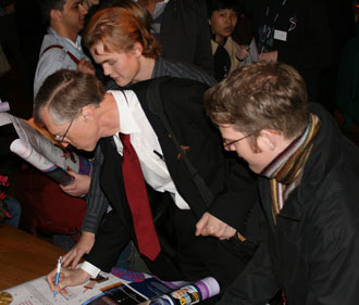 Nobel recipient John Mather autographs posters for students at the University of Stockholm, Sweden.