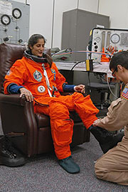 KSC-06PD-2585 -- Mission Specialist Sunita Williams is helped with her boot