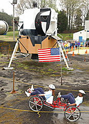 A moonbuggy in front of a lunar lander model