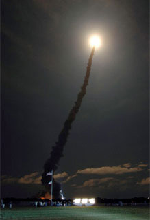 Space Shuttle Discovery launches into the dark sky to begin the STS-116 mission.