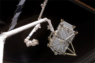 The P5 integrated truss segment is handed off from Discovery's robotic arm to the station's arm.