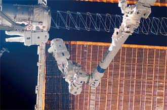 Mission Specialists Robert Curbeam and Christer Fuglesang work with the port overhead solar array wing on the station's P6 truss.