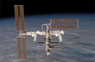 After undocking, the International Space Station moves away from Discovery.