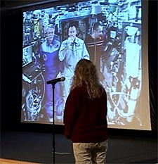 A student stands in front of a screen showing the crew of the ISS