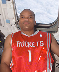 S116E07262 --- Robert Curbeam wearing red Rockets shirt on Space Shuttle Discovery.