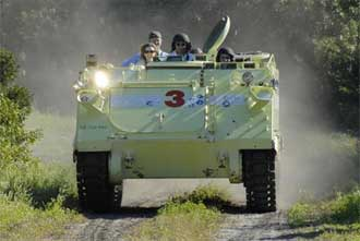 Members of the STS-117 crew practice driving an M-113 armored personnel carrier.