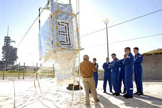 STS-117 crew members receive instruction on emergency egress using the slidewire basket system.