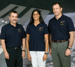 The Expedition 14 crew poses in front of a large picture of the space station