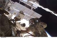 This photo shows an astronaut in a spacesuit and helmet manipulating levers outside the space station. Above his head is the underside of one of the solar panels.
