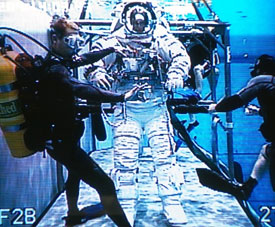 Divers assist an astronaut wearing a training version of an Extravehicular Mobility Unit space suit underwater