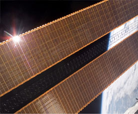Unfurled station solar array with Earth in background