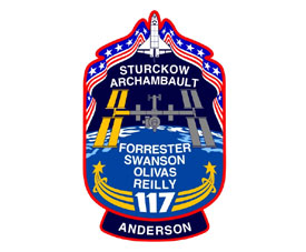The STS-117 mission patch includes the names of the crew and images of the shuttle and the station