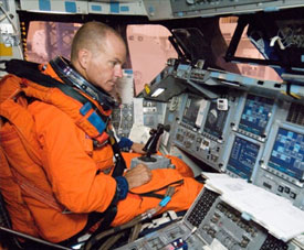 An astronaut sits in the space shuttle crew compartment trainer